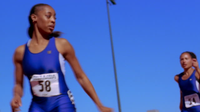 An athlete passes a baton to another runner in a relay race.