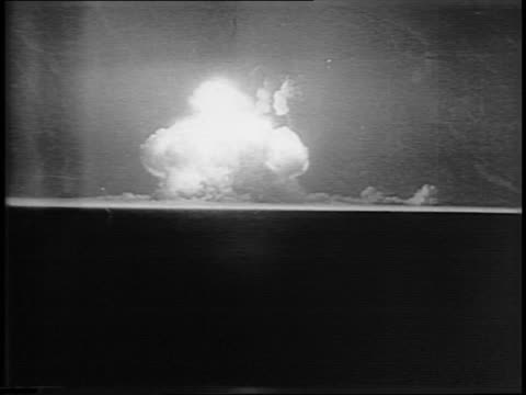 An atomic bomb detonates on the horizon mushroom cloud billowing into the sky / montage of aerial views of flattened Nagasaki