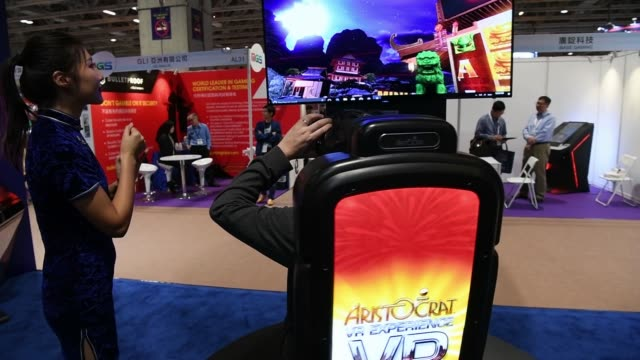 An attendee plays a virtual reality game by Aristocrat Technologies Australia Pty Ltd while wearing an HTC Corp Vive VR headset during the Macau...