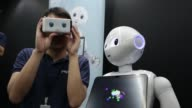 An attendee speaks with an attendant as they try out SoftBank Group Corp's Pepper the humanoid robot using a Google Inc Cardboard virtual reality...