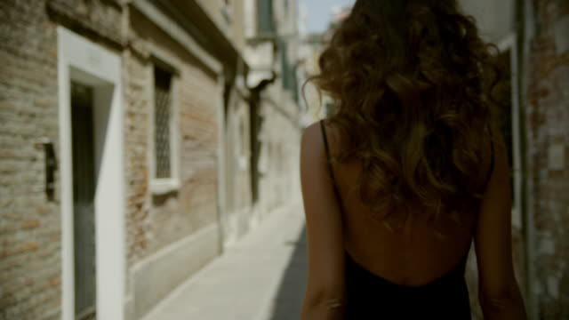 An attractive woman walks trough the streets of Venice
