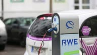 An automobile charging station operated by RWE AG stands connected to a Citroen CZero electric car sharing automobile manufactured by PSA Peugeot...