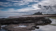 An early morning view across the rocks and beach with dramatic clouds building over Bamburgh Castle on the coastal shores of the North Sea
