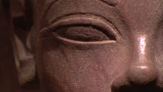 An Egyptian statue features a smooth carved eye and nose.