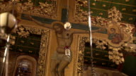 An elaborate gilded crucifix hangs from the ceiling of the Basilica of Saint Catherine's Monastery. Available in HD.
