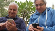 An elder couple busy with their respective phones sitting in the outdoor