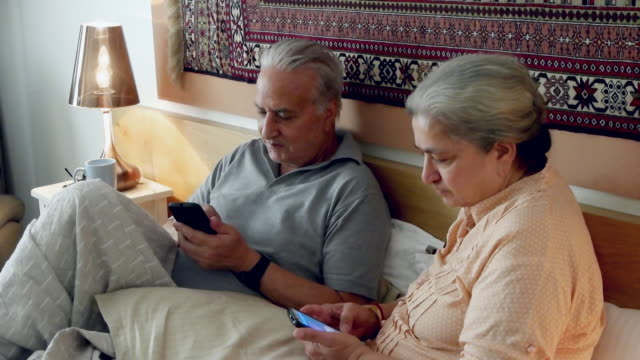 An elder Indian couple sharing and interacting with smartphone devices and enjoying a good laugh together in their bed.
