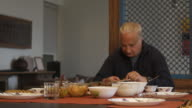 An elder mature gentleman sitting on a dining table