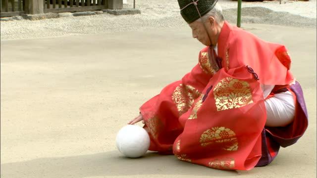 An elder places a ball during the Kemari Hajime at Shimogamo Shrine.