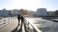 An elderly couple watches the view from the pier to the sea resort and Grand Hotel Heiligendamm at the baltic sea on a sunny autumn day Also known as...