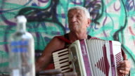 An elderly man plays the accordion in front of a graffiti wall.