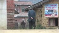 An elderly man walks along a dirt road in Guangxi, China.