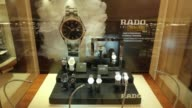 An employee arranges luxury wrist watches in a Rado display cabinet inside the Sublime by Bosco di Ciliegi retail unit at the GUM department store on...