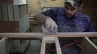An employee at Colonial House Reproduction Furniture in Auburn Kentucky removes wood furniture pieces from a conveyor belt A middleaged white male...