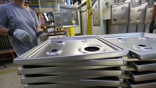 An employee attaches steel oven tops to hooks on the production line at the Gorenje dd home appliances factory in Velenje An employee works on...