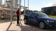 An employee holds a pump as an Audi A3 gtron automobile is refueled with egas at Audi AG's powertogas plant which uses electricity from wind turbines...