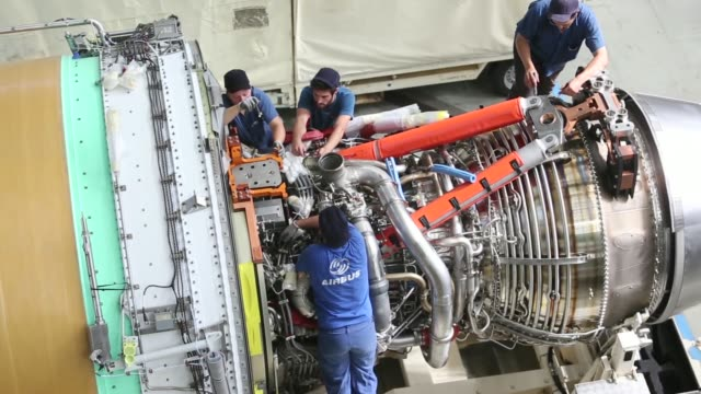 An employee inspects a Rolls Royce Trent 900 aircraft engine manufactured by Rolls Royce Holdings Plc as it sits on the Airbus A380 aircraft assembly...