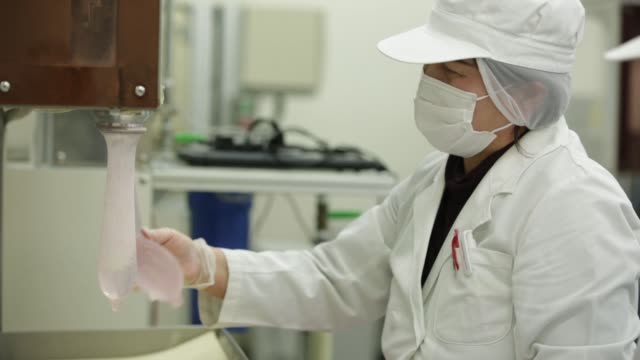 An employee inspects latex condoms during a water leaking test at a Sagami Rubber Industries Co factory in Atsugi Kanagawa Prefecture Japan on...