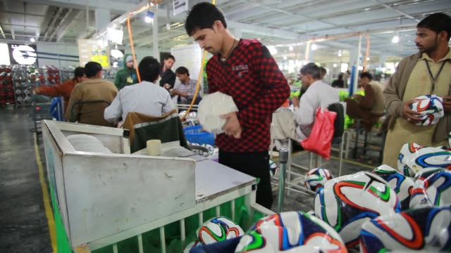 An employee inverts a machine stitched Brazuka Replica soccer ball An employee inserts a bladder into Brazuka Replica soccer ball An employee hand...
