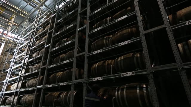 An employee looks on as barrels of aged distilled water for making soju sit stacked inside the warehouse of the Hite Jinro Co factory in Icheon tilt...