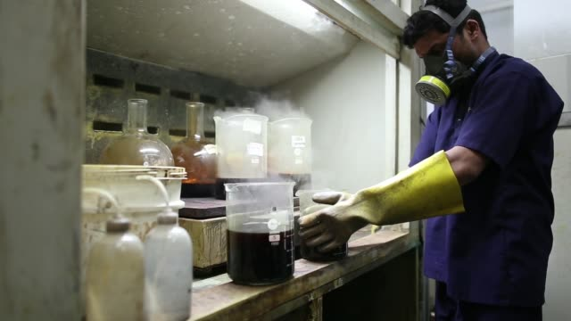 An employee monitors beakers containing aqua regia or nitrohydrochloric acid as they dissolve gold inside the gold refinery unit at Kama Schachter...