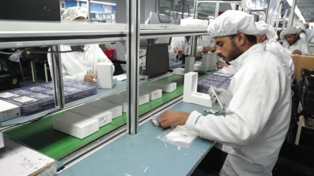 An employee packs a smartphone into a box on the production line inside the Intex Technologies India Ltd plant in Noida Uttar Pradesh India on Friday...