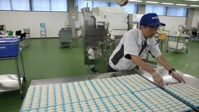 An employee places a mold tray of sushi rice made by a Suzumo Machinery Co sushi machine on a table during a demonstration at the company's factory...