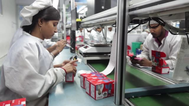 An employee places cases of smartphones onto a machine at a packing area inside the Intex Technologies India Ltd plant in Noida Uttar Pradesh India...