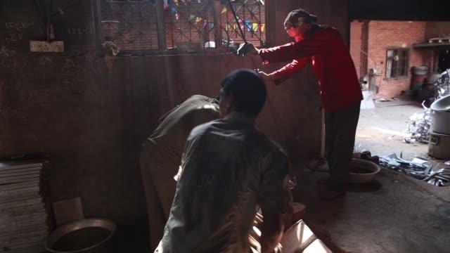 An employee pours molten aluminum onto plate molds at Balaju Aluminium Industry's factory in Kathmandu Nepal