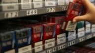 An employee replenishes packs of cigarettes in a display rack behind the counter inside a newsagents store in London UK on Friday July 11 An employee...