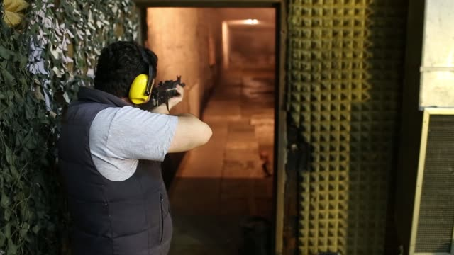 An employee shoots a M21A NATO standard assault rifle on a firing range at the Zastava Oruzje AD firearms factory in Kragujevac Serbia on Tuesday Oct...