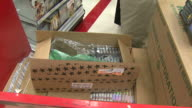 TU An employee stacking a shelf with CDs in a busy Target store / United States