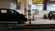 An employee stands next to a gas pump as a vehicle is refueled at a PetroChina Co gas station at night in Hong Kong China on Monday Aug 21 An...