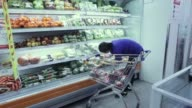 An employee stocks the shelves of a chilled goods section at a Nomin Holding supermarket in Ulaanbaatar Mongolia on Saturday Aug 12 Customers browse...