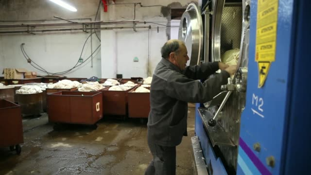 An employee unloads a Maino FRC 120 washing machine during the felting process inside the factory of 174yearold beretmaker Laulhere owned by French...