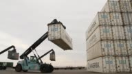 An employee uses a container crane to stack a Maersk Sealandbranded shipping container on the dockside at the AP Moeller Maersk A/S container...