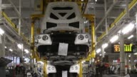 An employee uses a crane to move an engine and drive train assembly for a Bentley Continental automobile to a trolley as he works on the production...
