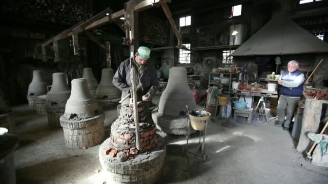 An employee works on the hook for a bell at Fonderia Pontificia Marinelli foundry in Agnone Italy on Monday Nov 11 An employee works on the casing...