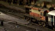 An engine pulls a passenger train into a station. Available in HD