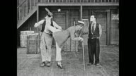 An enthusiastic vaudeville dancer (Jack Coogan Sr.) accidentally kicks Al St John to the ground and knocks the hat off of a sweeping Fatty Arbuckle's head