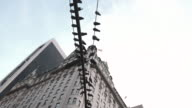 An establishing shot of pigeons perched on a New York City lamp post.