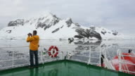 An ice strengthened expedition cruise ship in stunning coastal scenery in Paradise Bay off Graham Land on the antarctic Peninsular. the Peninsular is one of the most rapidly warming places on the planet.