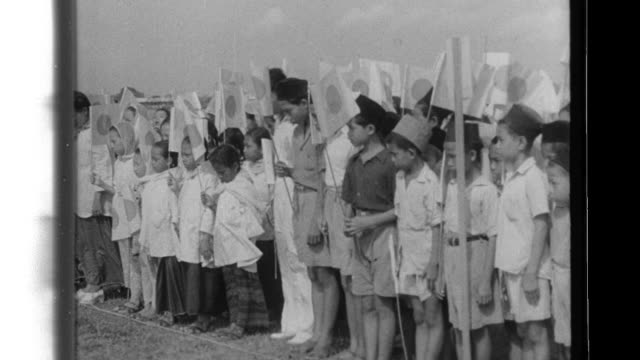 An Imperial Japanese Army officer thanks Malay civilians for their donations which paid for Type I Hayabusa fighter 3948 and the Malays cheer as the...