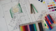An interior designer clearing his table of his drawings, coloured pencils and other tools