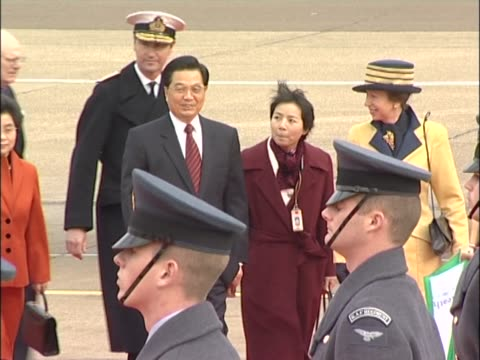 An interpreter rushes to keep up with Princess Anne and Chinese leader Hu Jintao as they walk past RAF guard of honour at Heathrow at the start of...