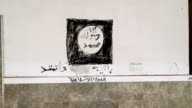 An Islamic State flag painted on the wall of a church in the predominantly Christian village of Bartella during the occupation by ISIS is seen after...
