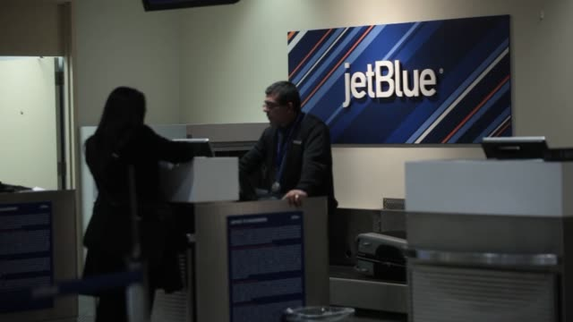 An Jet Blue employee assists a traveler at the checkin counter at Ronald Reagan National Airport in Washington DC US on Thursday Jan 23 Various Jet...