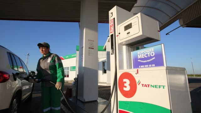 An OAO Tatneft gas station at the highway M7 'Volga' near Kazan Republic of Tatarstan Russia August 2 2015 Shots Gas attendant filling up x 2 wide...