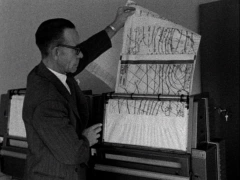 An office worker collects a meterological map from a printer at the Met Offices new office in Berkshire 1961