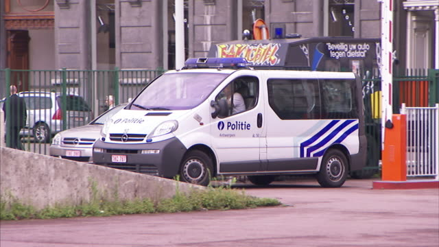 An officer drives a police vehicle past parked cars in Antwerp, Belgium.